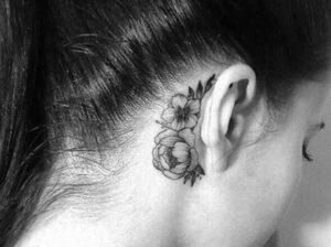 tatuaje femenino rosas detrás de la oreja